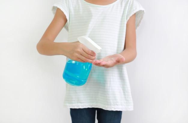 병 스프레이 알코올 액체를 사용하여 흰색 배경, 방부제에 격리된 코로나바이러스 전염병 발병에 대항하기 위해 손을 대는 어린이. 아이 손에 선택적 초점