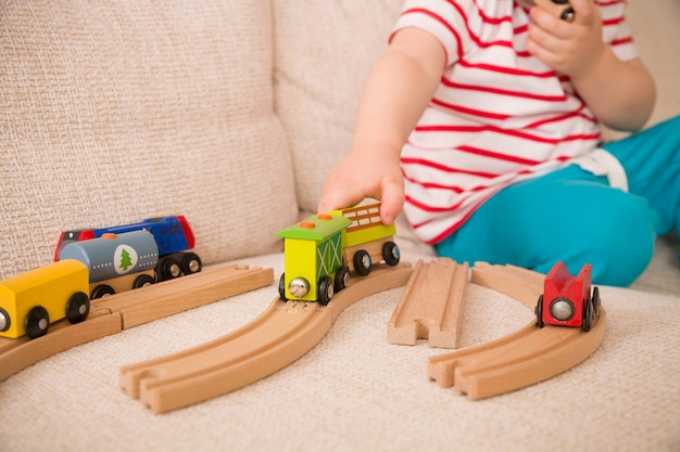 Closeup of childs hands playing with wooden toys train and railroad on sofa