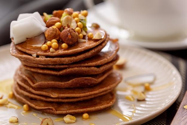 Шоколадные оладьи крупным планом в бежевой тарелке с орехами, киви и кокосовой стружкой