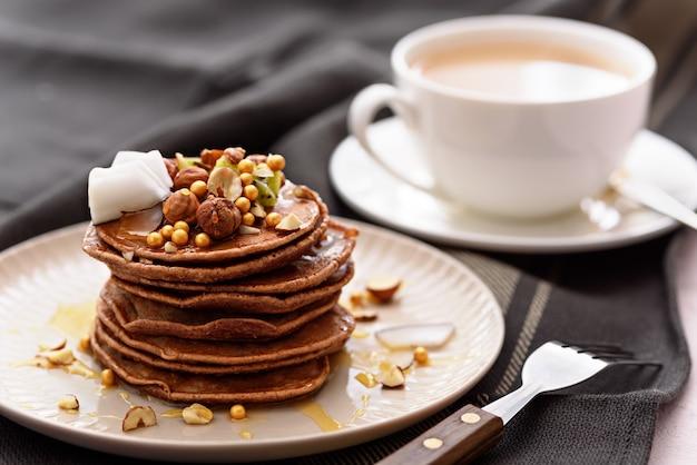 Шоколадные блины крупным планом с киви, лесным орехом, медом, кокосовой стружкой на тарелке с вилкой и чашкой чая или кофе на сером фоне полотенца