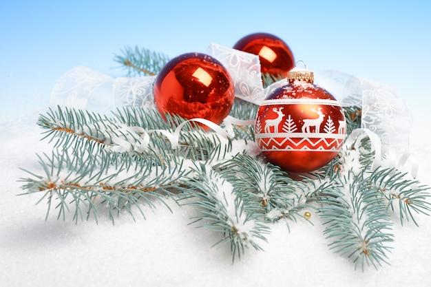 Closeup on christmas balls with raindeer ornament on fir twigs under snow