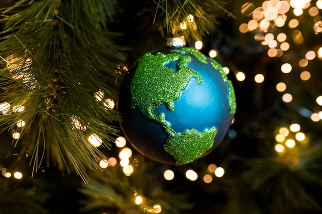 Closeup of christmas bauble decoration ornament planet earth on the background of the christmas
