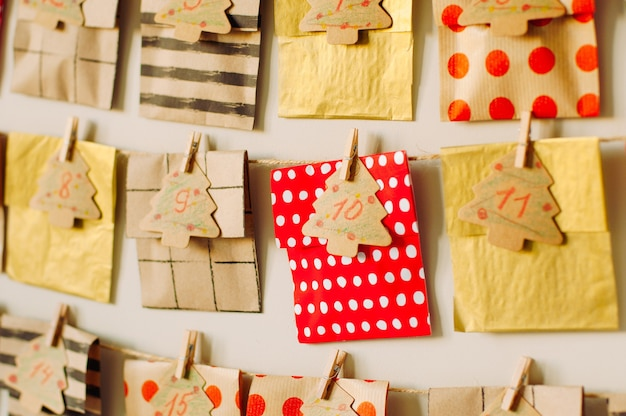 Closeup of the christmas handmade advent 24-days calendar of paper envelopes on the wall in the kids room