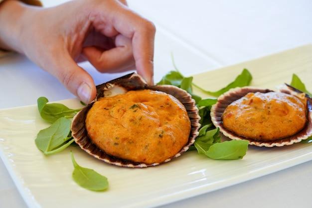 Primo piano di vongole con gamberetti, cipolla e salsa di peperoni