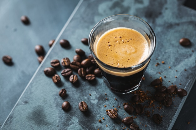 Closeup of classic fresh espresso served on dark surface.