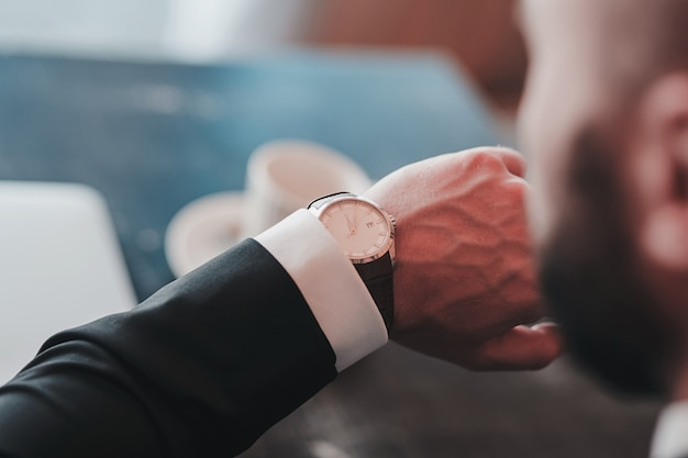 ビジネスマンの手にクローズアップの古典的な時計、彼は時間を見て
