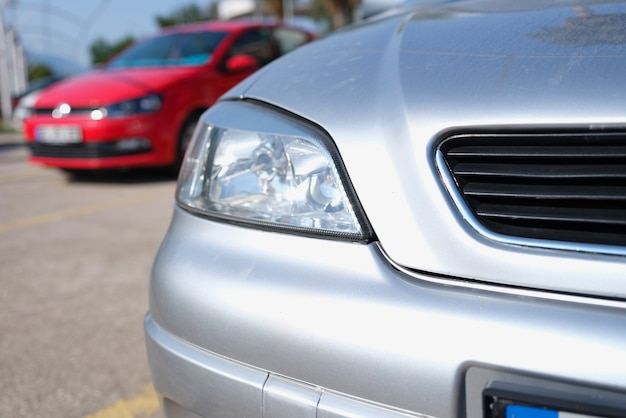 Closeup of clean headlights of silvery car in parking