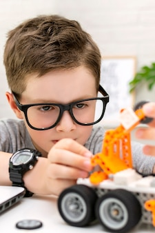 Closeup of a clever boy in eyeglasses builds and programs a robot car at home the child is learning ...