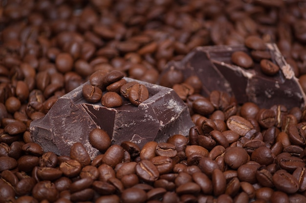 Closeup of coffee beans and chocolate pieces background.