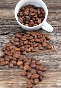 음료를 위한 전체 형태의 커피 콩, 컵에 담긴 향기로운 커피 콩, 머그에 맛있는 커피를 만들기 위한 커피 콩