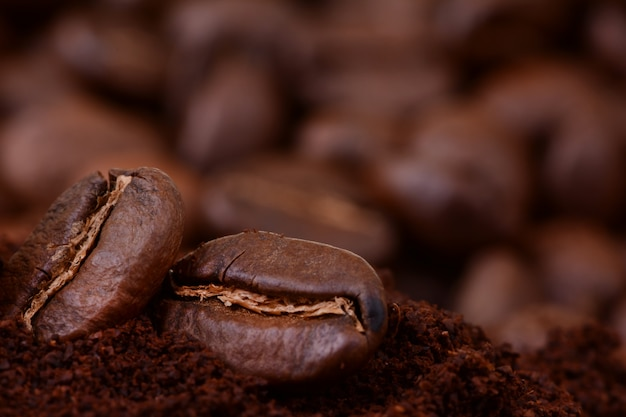 Closeup of coffee beans at roasted coffee heap. coffee bean on macro ground coffee background. arabic roasting coffee - ingredient of hot beverage
