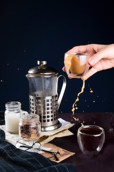 Closeup of coffee, french press, glasses and women hand holding cup with splashing beverage, selective focus