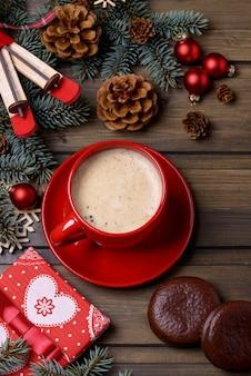 赤いカップとギフトボックスのクリスマスカードのクローズアップコーヒー