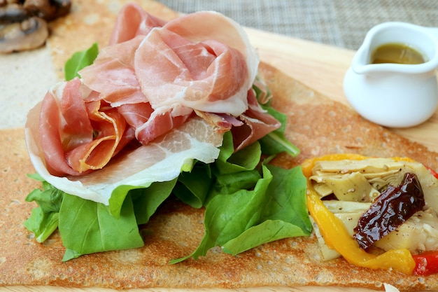 Closeup cold cuts ham with fresh and saute vegetables of an european appetizer crepe