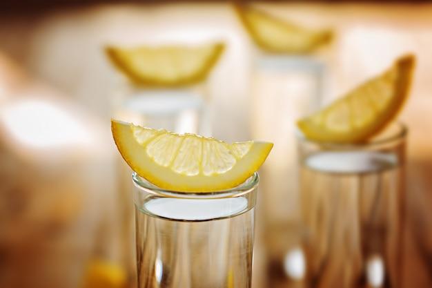 Closeup cold glass of vodka with lemon.