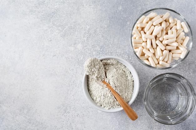 古い灰色のコンクリートテーブルの上のダイエット食品、ヘチマスポンジ、乾燥したユーカリの枝のためのスプーンとカプセルを備えたセラミックボウルで化粧品マスクを準備するためのクローズアップコラーゲン。フラットレイ