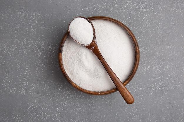 スプーンで木の板にコラーゲン粉末をクローズアップするか、コンクリート表面の量を測定します。 f余分なタンパク質摂取。美容のための天然サプリメント。
