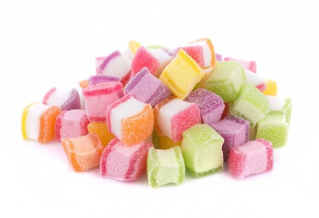 Крупным планом красочные конфеты и желе сладкое на белом