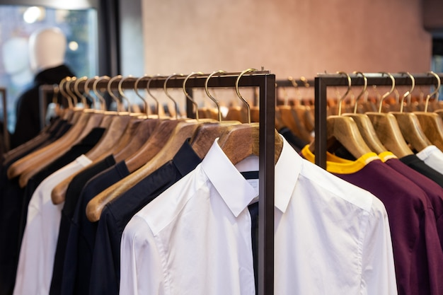 Closeup colorful male, female clothes in boutique hanging on hangers, clothing rack on metal stand. concept opening luxury shop, shopping mall, store sale, retail fashion store, second hand outlet.
