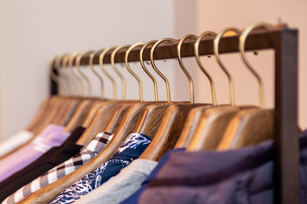 クローズアップカラフルな男性、女性の服をハンガーに掛かっているブティックで服、金属製のスタンドのラック。高級店、ショッピングモール、店舗の販売、小売店、セカンドハンドアウトレットを開くコンセプト。