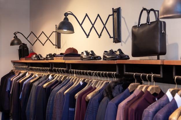 クローズアップカラフルな男性、女性の服、ハンガー、洋服ラックに掛かっているブティックの靴。高級店、ショッピングモール、店舗の販売、小売店、セカンドハンドアウトレットを開くコンセプト。