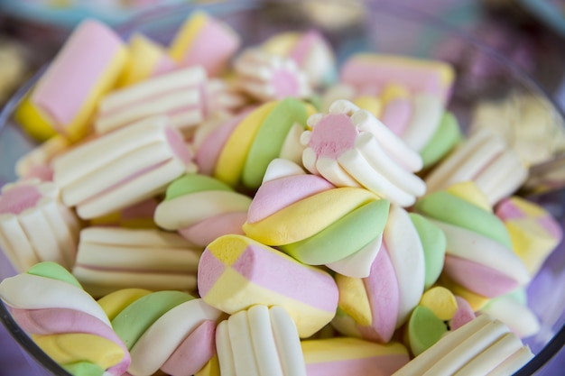 Primo piano di marshmallow colorati in una ciotola sotto le luci