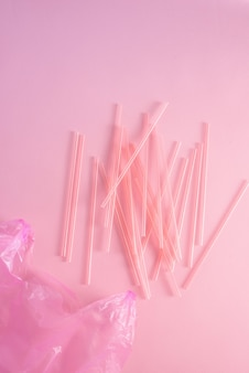 Closeup of colorful plastic waste in a pink garbage bag as recyclable single use cutlery pollution junk concept isolated on pink background