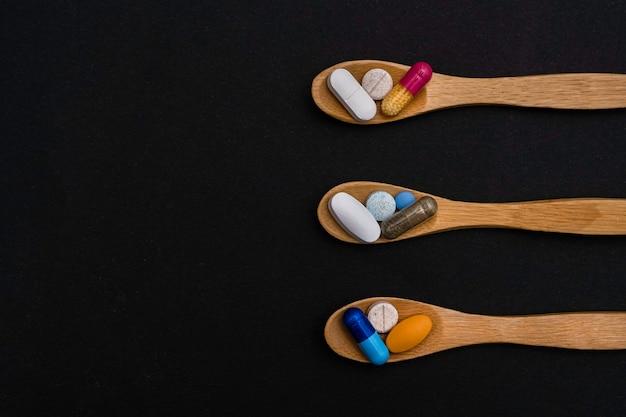 근접 촬영 다채로운 분말 소프트 캡슐 알약 나무 숟가락 파란색 분홍색 노란색 갈색 보충 비타민