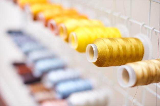 바느질 장비, 직물 및 섬유 산업, 자수 기계, 아무도에 스레드의 근접 촬영 다채로운 스풀