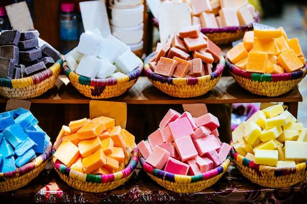 Primo piano di dolci colorati in ciotole sugli scaffali sotto le luci in un mercato