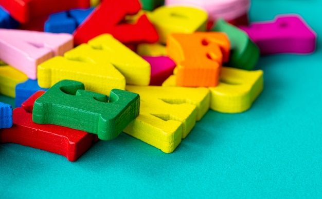 Closeup of colorful wooden alphabet on green background.