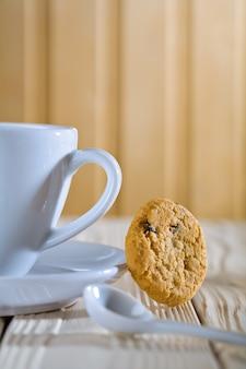 Состав крупного плана. синяя кофейная чашка с ложкой и печеньем
