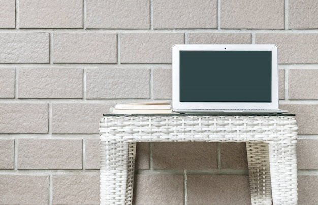 Closeup computer on blurred wood weave table and brown brick wall