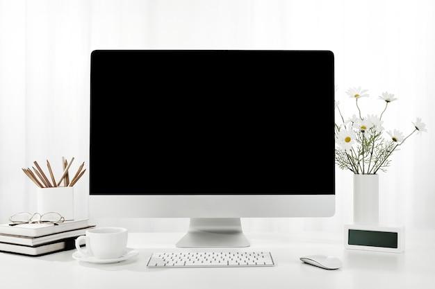 Primo piano di un computer, una tazza di caffè, un vaso di fiori e altro su una scrivania bianca, al chiuso