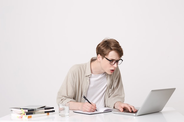 Closeup of concentrated young man student wears glasses and beige shirt sitting and working with laptop computer and notebooks at the table isolated over white wall