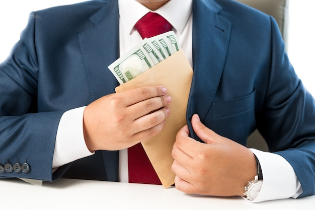 Closeup conceptual bribed man putting money in the suit pocket