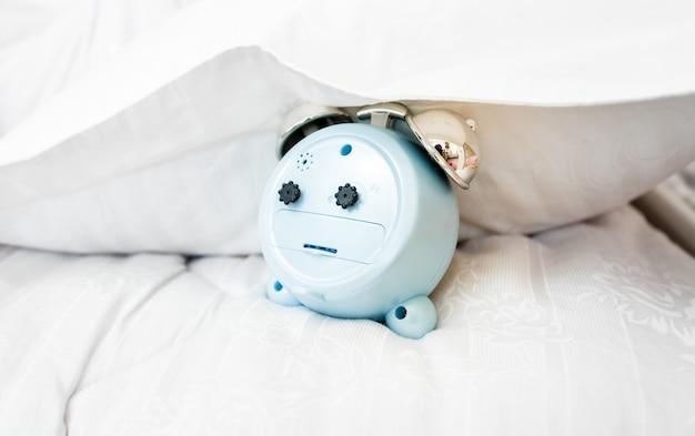 Closeup conceptual photo of alarm clock under pillow on bed