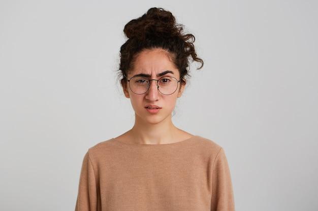 Primo piano della giovane donna infelice confusa con il panino dei capelli ricci scuri