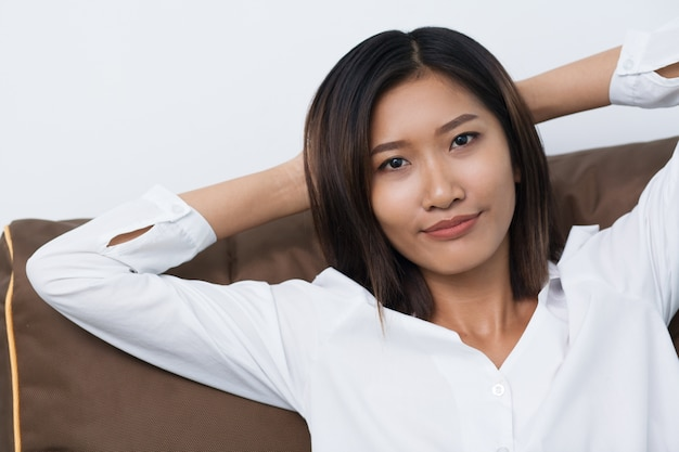 Closeup of content asian woman resting on cushion