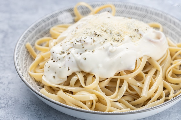 Closeup of cooked fettuccine with cream and spices in a bowl under the lights