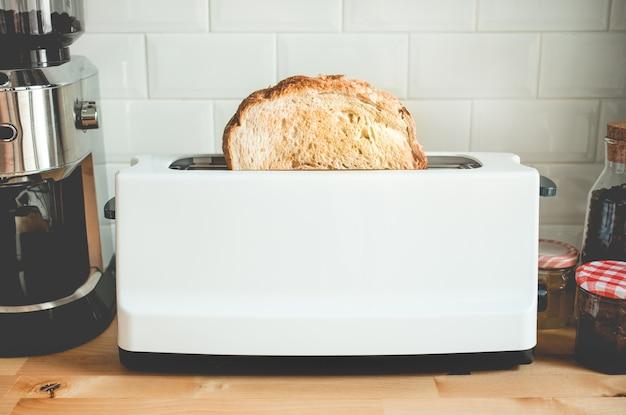 Крупным планом приготовление хлеба с тостером на кухне барной стойки утром