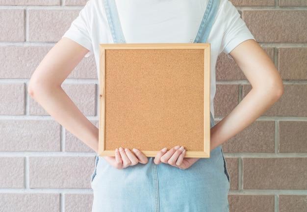 Closeup cork board in hand of woman in backside
