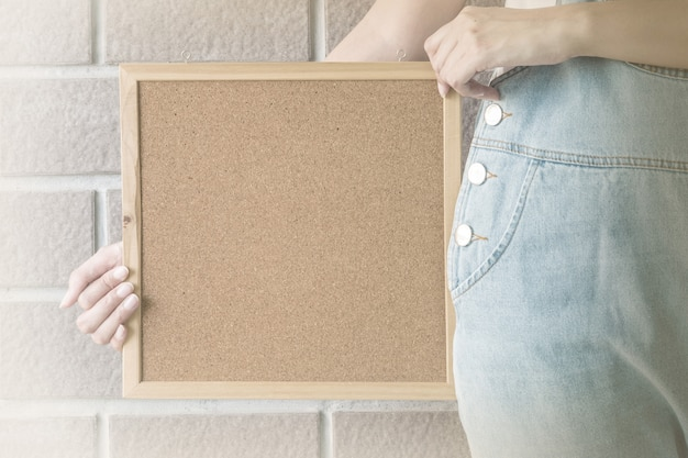 Closeup cork board in hand of woman beside the body