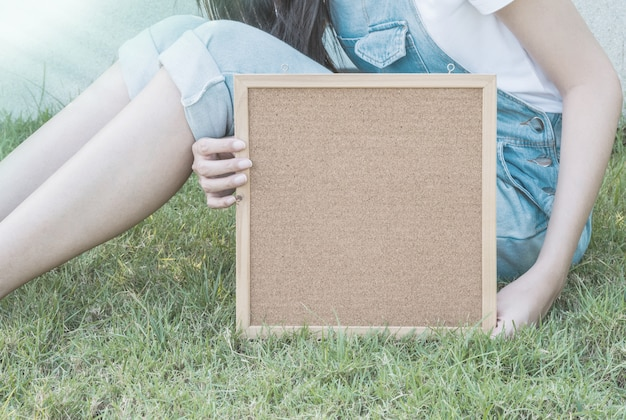 Closeup cork board in hand of woman beside the body