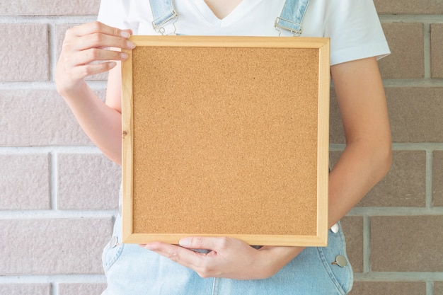 Closeup cork board in hand of woman in front of body