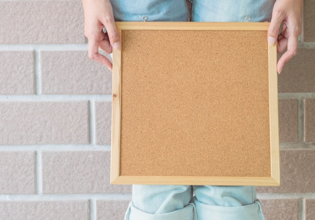 Closeup cork board in hand of woman in front of her legs