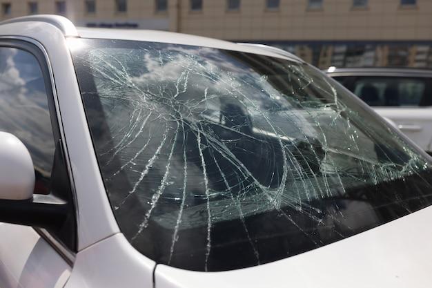 Closeup of cracks on broken car windshield car insurance concept
