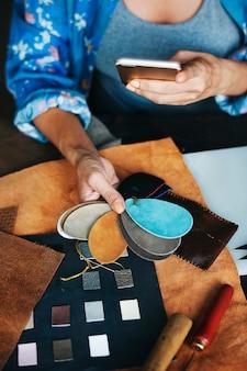 Closeup of craftsman choosing leather handicraft