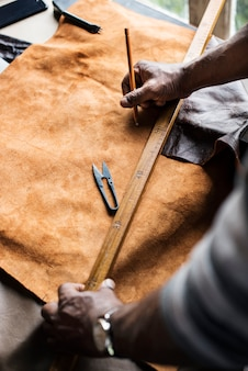 Closeup of craftsman measuring leather handicraft