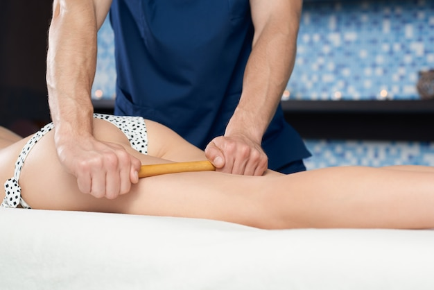Closeup of creole massage with bamboo sticks in spa salon